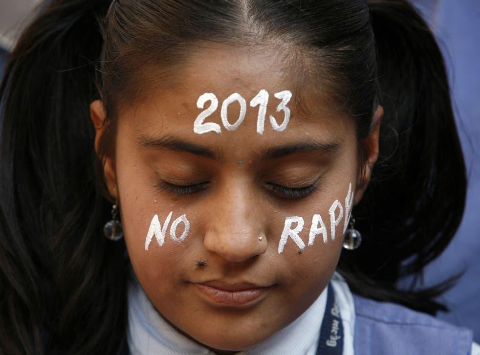 A student prays during a vigil in New Delhi