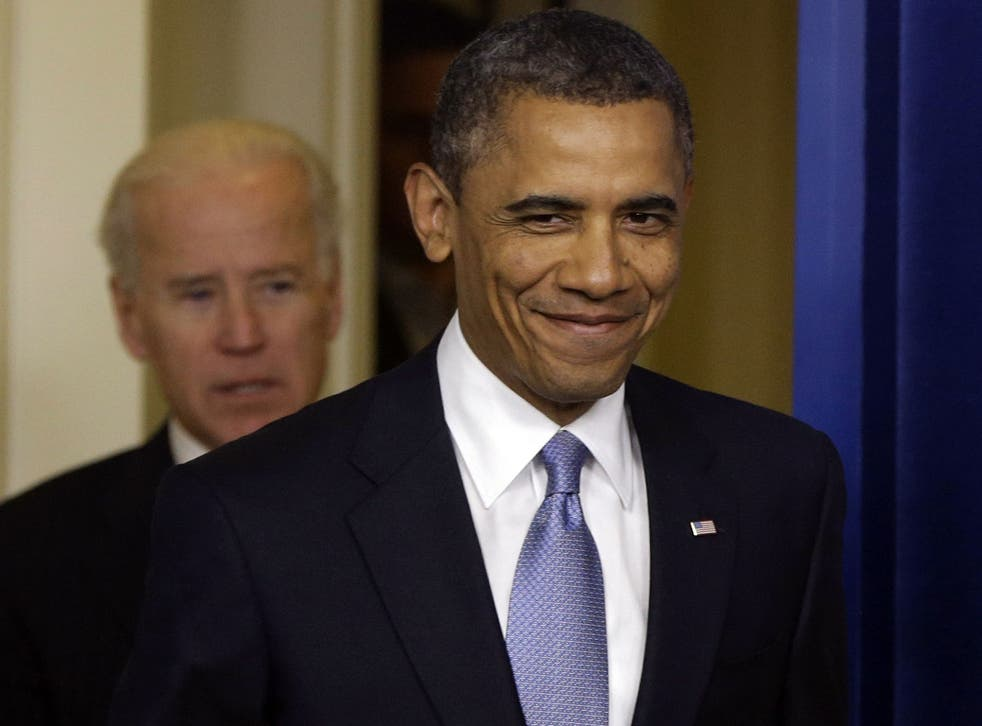 President Barack Obama smiles as he arrives with Vice President Joe Biden to make a statement the fiscal cliff bill is passed