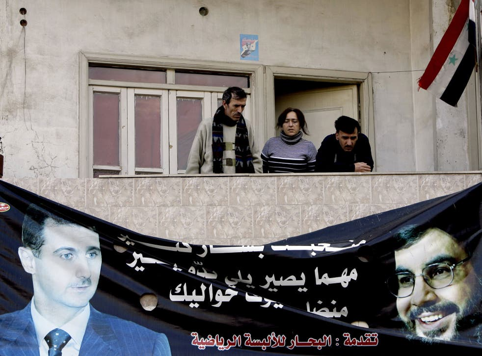 Syrians stand above a poster of Syrian President Bashar al-Assad (L) and Lebanese Hezbollah Leader Hassan Nasrallah (R) hanging on the wall of a building in the Alawite neighbourhood of Nuzhah in the western city of Homs, 162 kms north of Damascus, on January 11, 2012.