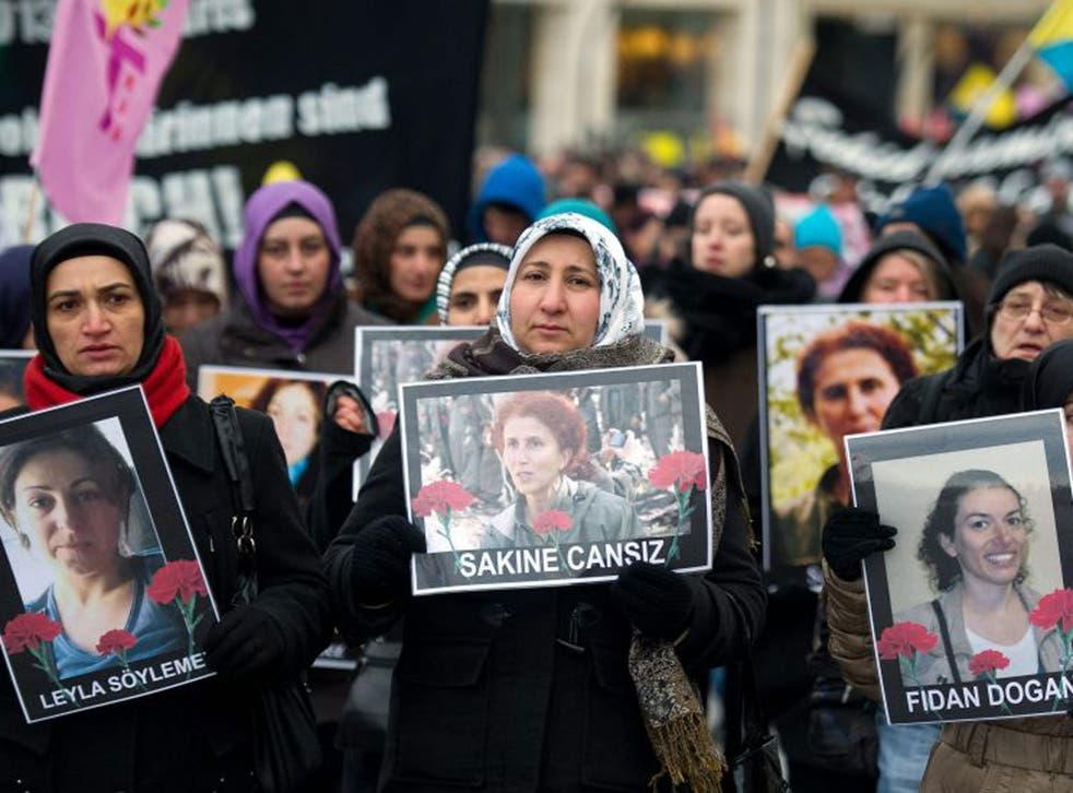 Members of Kurdish organizations carry pictures of three murdered female Kurdish activists during a demonstration in Hamburg