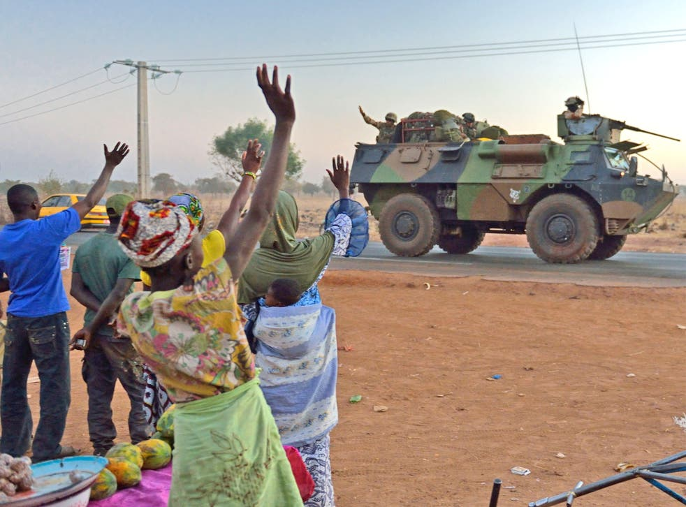 Malians wave to French soldiers as a convoy leaves Bamako. More troops and equipment were arriving yesterday