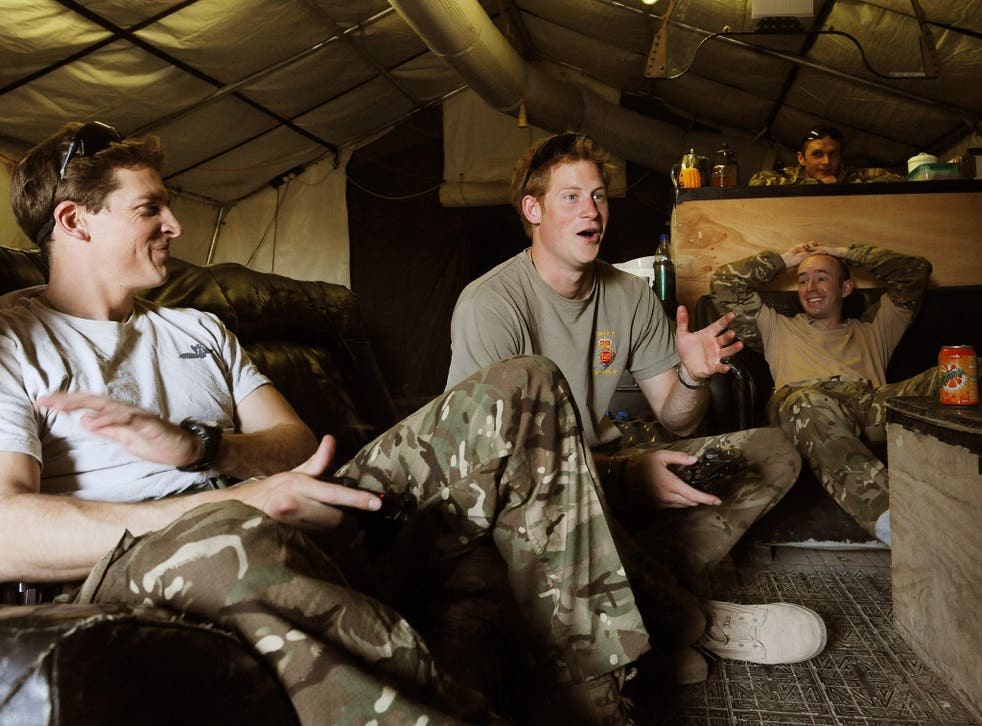 Prince Harry relaxes after scoring a goal during a computer football game with his fellow Apache Helicopter Pilot Capt Simon Beattie (left), during their 12 hour VHR (very high readiness) shift