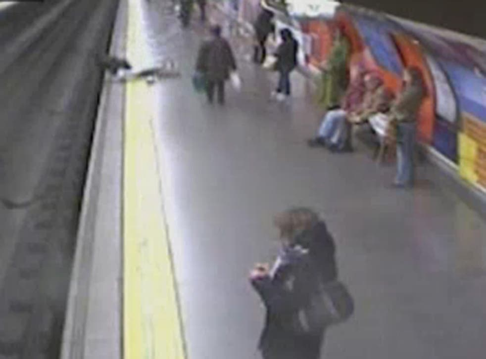 A woman faints on the yellow line shortly before falling onto the tracks