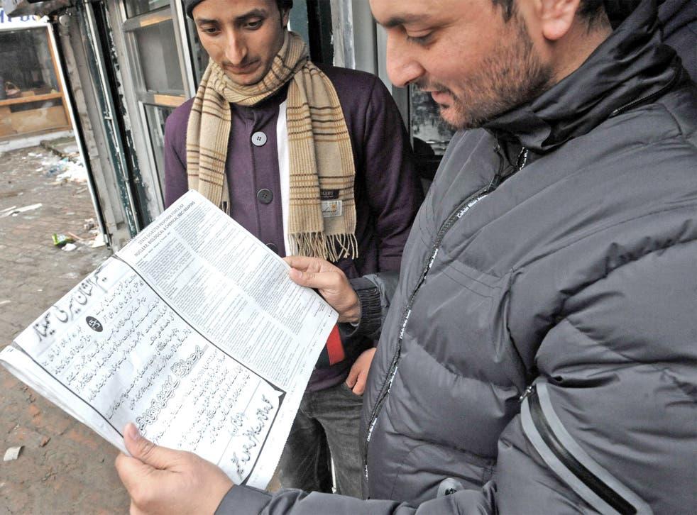 Kashmiri residents read the instructions