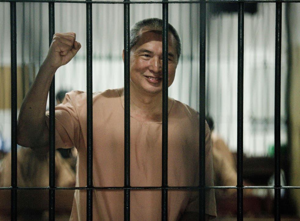 Activist Somyot Prueksakasemsuk reacts as he arrives at the criminal court in Bangkok