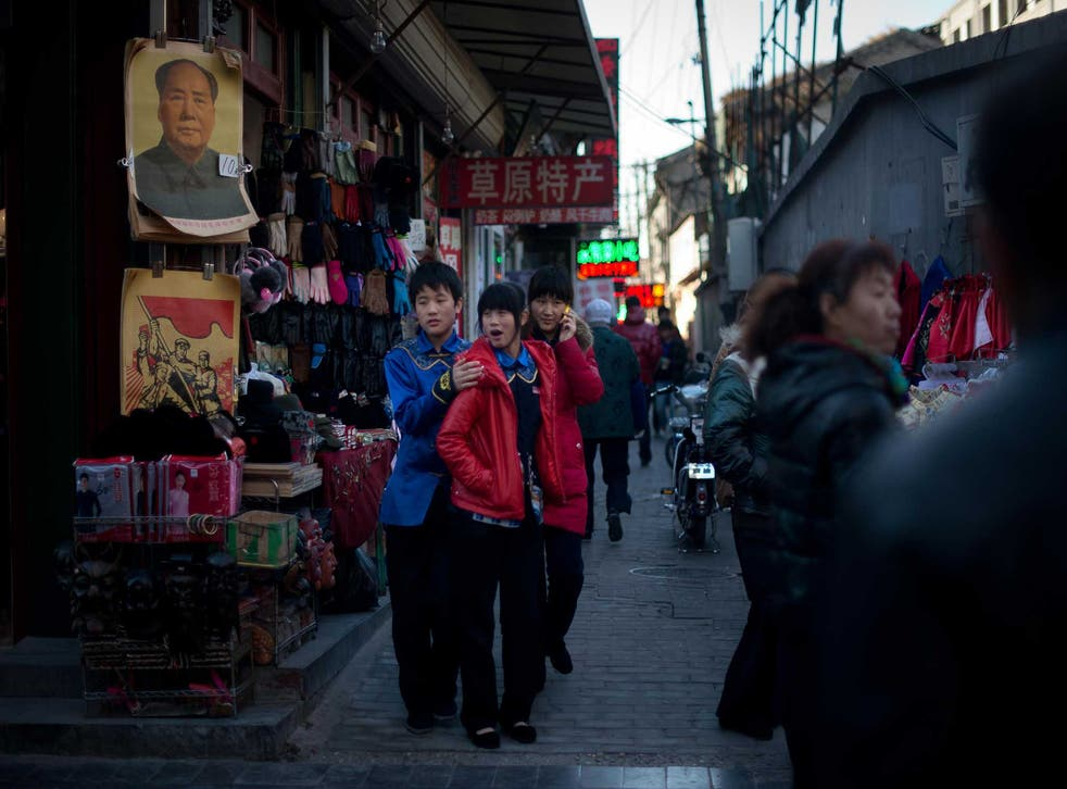 The deadly idol: a poster of Mao in a street in Qianmen, Beijing