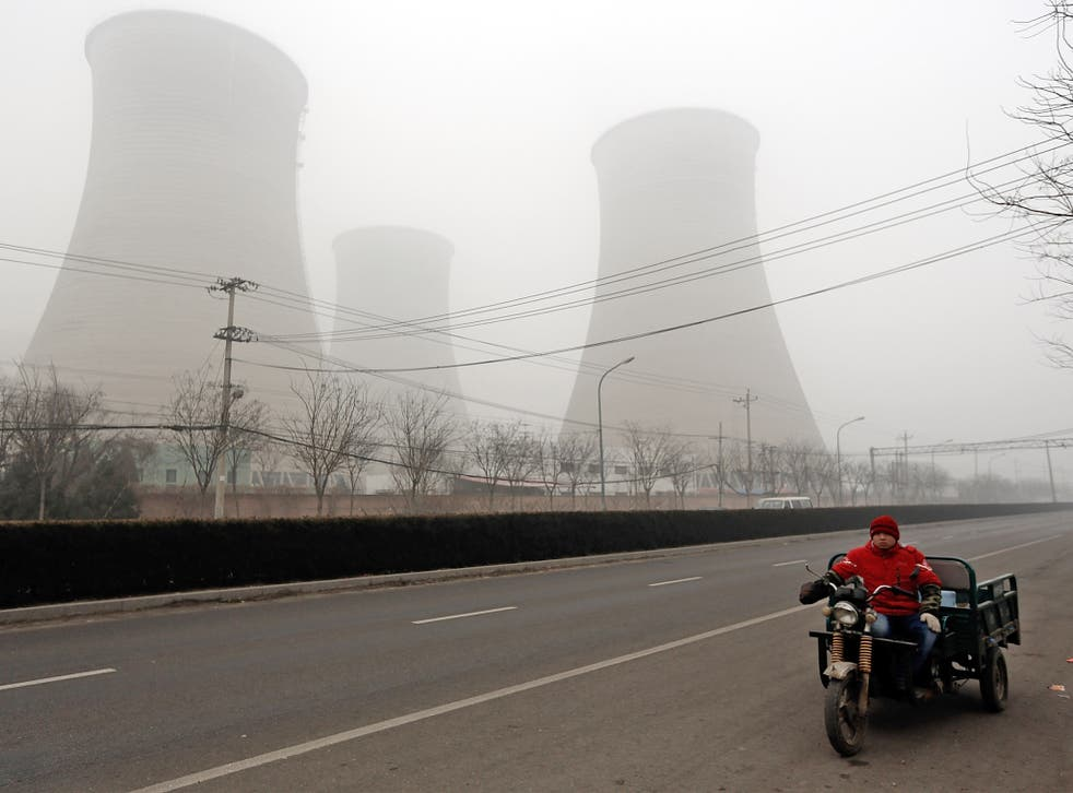 A men rides a three-wheeled motorcycle past power station chimneys. Heavy industry is the main cause of the pollution
