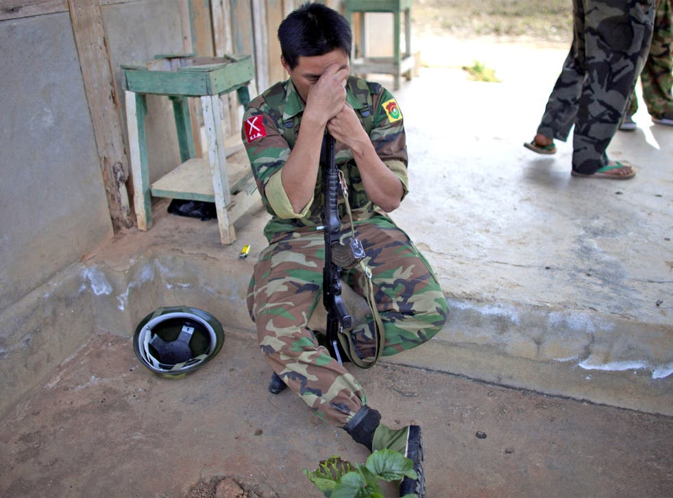 A Kachin soldier rests on his gun amid a lull in fighting yesterday