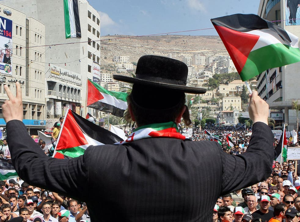 A member of Neturei Karta, a small faction of ultra-Orthodox Jews who oppose Israel's existence, wave a Palestinian flag to express support for the Palestinian bid for statehood recognition at the UN as thousands of Palestinians attend a demonstration on September 21, 2011 in the West Bank city of Nablus.