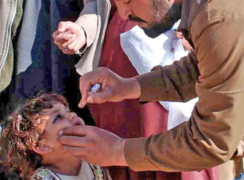 A vaccinator inoculates a child against polio in Pakistan