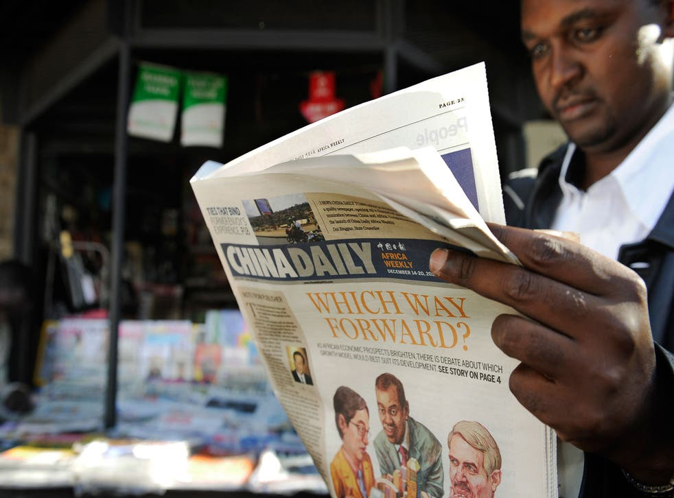 A newspaper consumer reads a copy of China's Africa edition of its daily newspaper infront of a news stand in the Kenyan capital