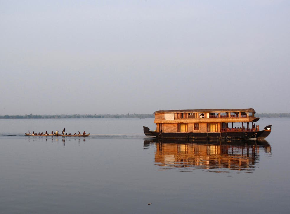 Go with flow: A houseboat tows a fishing boat on Lake Vembanadu in Kerala