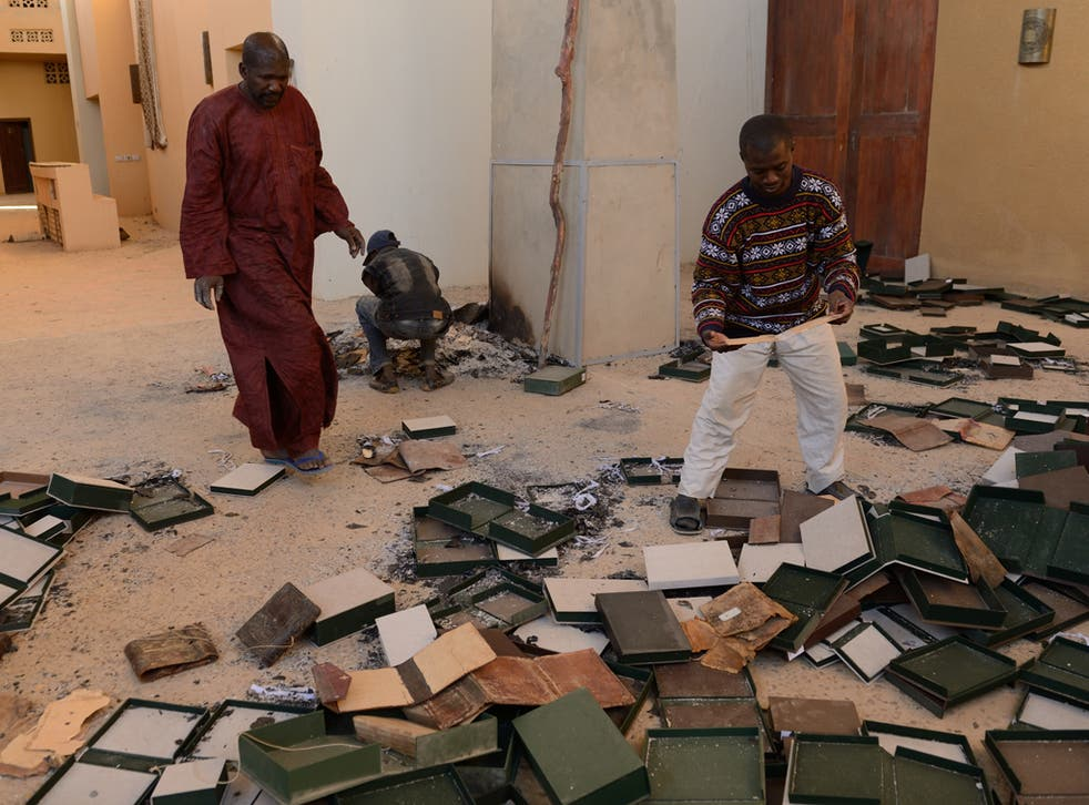 Men recover burnt ancient manuscripts at the Ahmed Baba Centre for Documentation and Research in Timbuktu