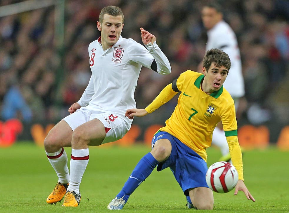 Jack Wilshere (left) and Oscar tussle for the ball at Wembley last night