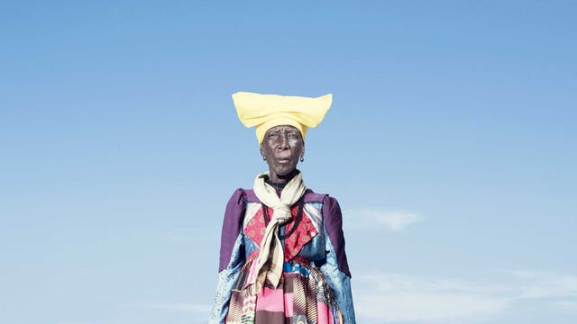 An elderly Herero woman in a patchwork dress that would be worn every day of the year; as Herero women get older, the 'horns' of their headdresses get smaller. According to some accounts, this symbolises their loss of fertility