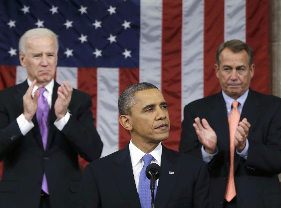US House Speaker John Boehner (right) and Vice President Joe Biden (left) stand to applaud as President Barack Obama delivers his State of the Union speech