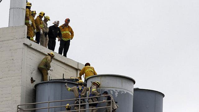 Los Angeles firefighters examine tanks on the roof of the Hotel Cecil