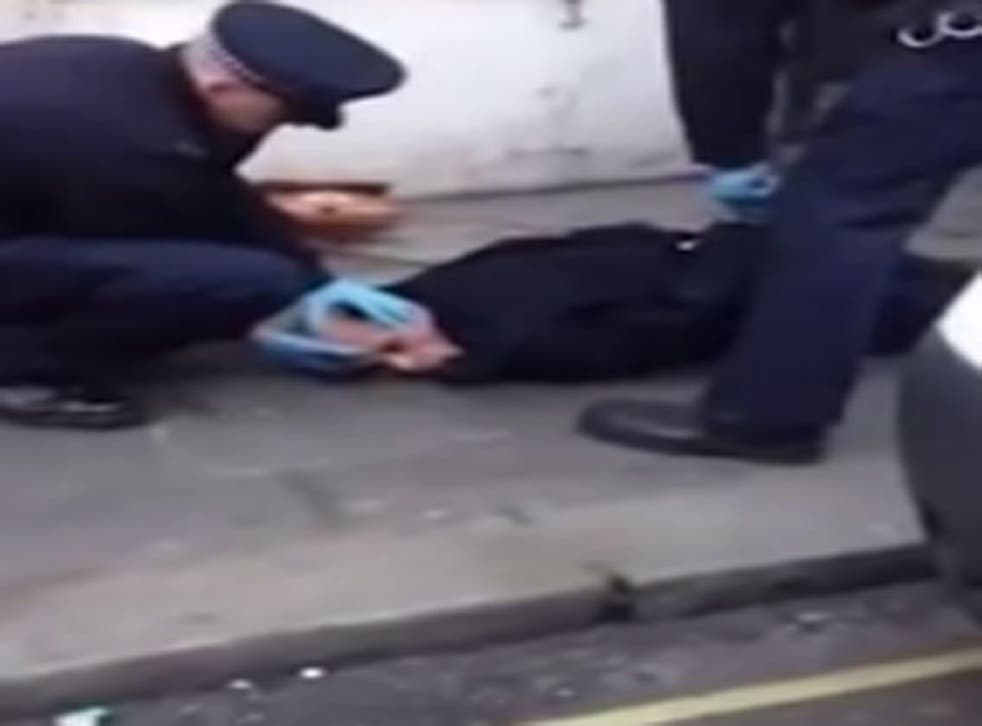A shot from the video showing the transgendered woman being held down by police
