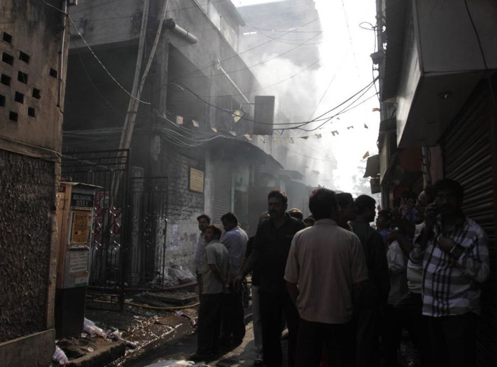 Residents and onlookers wait outside the smoldering buildings where the fire broke out
