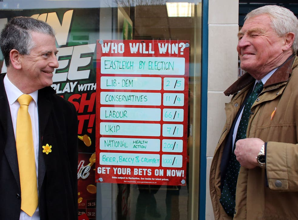 Former Liberal Democrat leader Lord Paddy Ashdown (R) stands beside a bookmakers' odds for the election as he campaigns with Liberal Democrat candidate Mike Thornton (L) for the forthcoming by-election on February 26, 2013 in Eastleigh, England.
