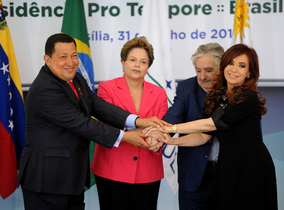 Brazilian President Dilma Rousseff (2nd-L) holds hands with the presidents of Uruguay, Jose Mujica (2nd- R), Argentina, Cristina Kirchner (R), and Venezuela, Hugo Chavez ( L), before the Mercosur Extraordinary Summit, at Planalto Palace, in Brasilia, on July 31, 2012.