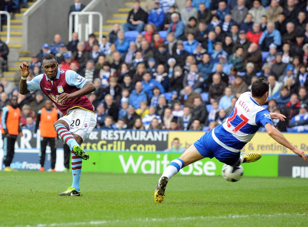 Christian Benteke of Aston Villa shoots past Stephen Kelly of Reading to score their first goal