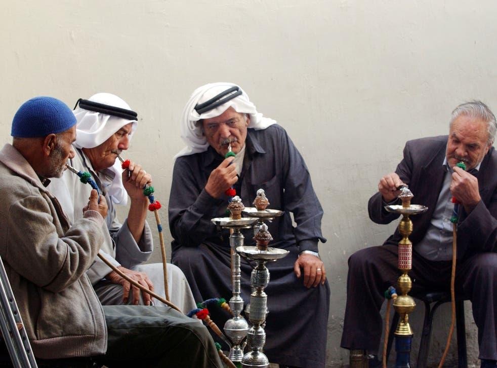 Jordanian men smoke nargile in a cafe October 22, 2002 in downtown Amman, Jordan.
