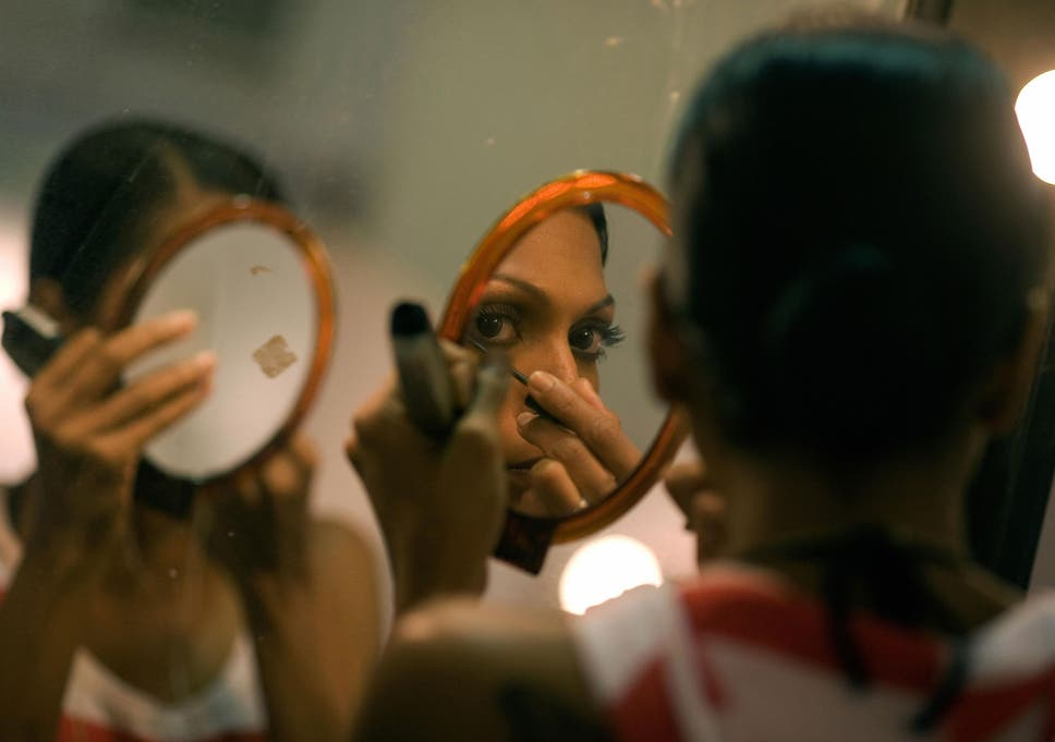 An Indian model is reflected in a mirror as she does her makeup before the Manav
