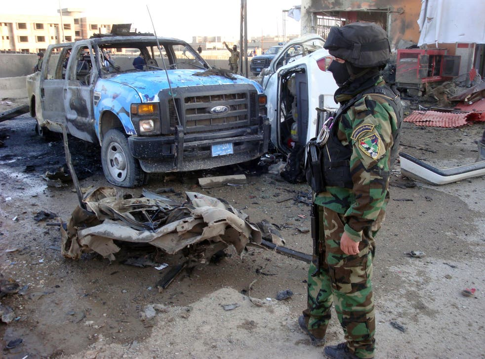 An Iraqi security office stands close to the debris following a car bomb, in the northern city of Kirkuk on March 5, 2013.