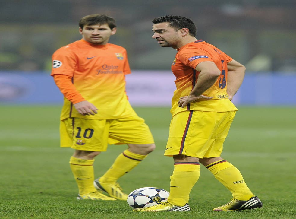 Barcelona duo Xavi and Lionel Messi pictured in the first leg against AC Milan