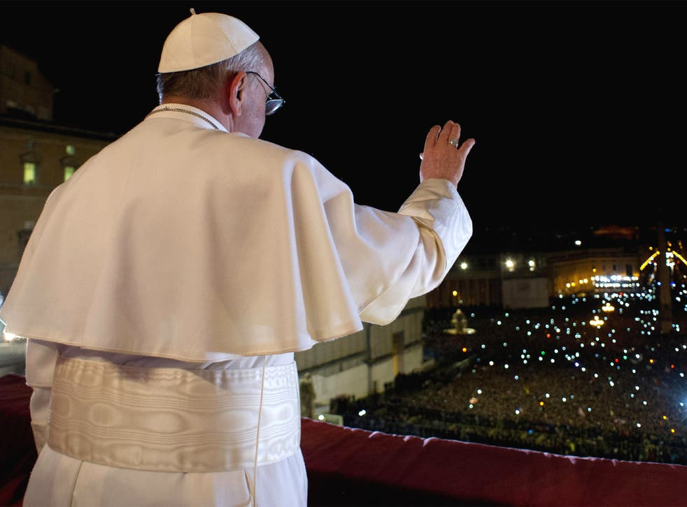 Pope Francis waves the crowd from the central balcony of St. Peter's Basilica