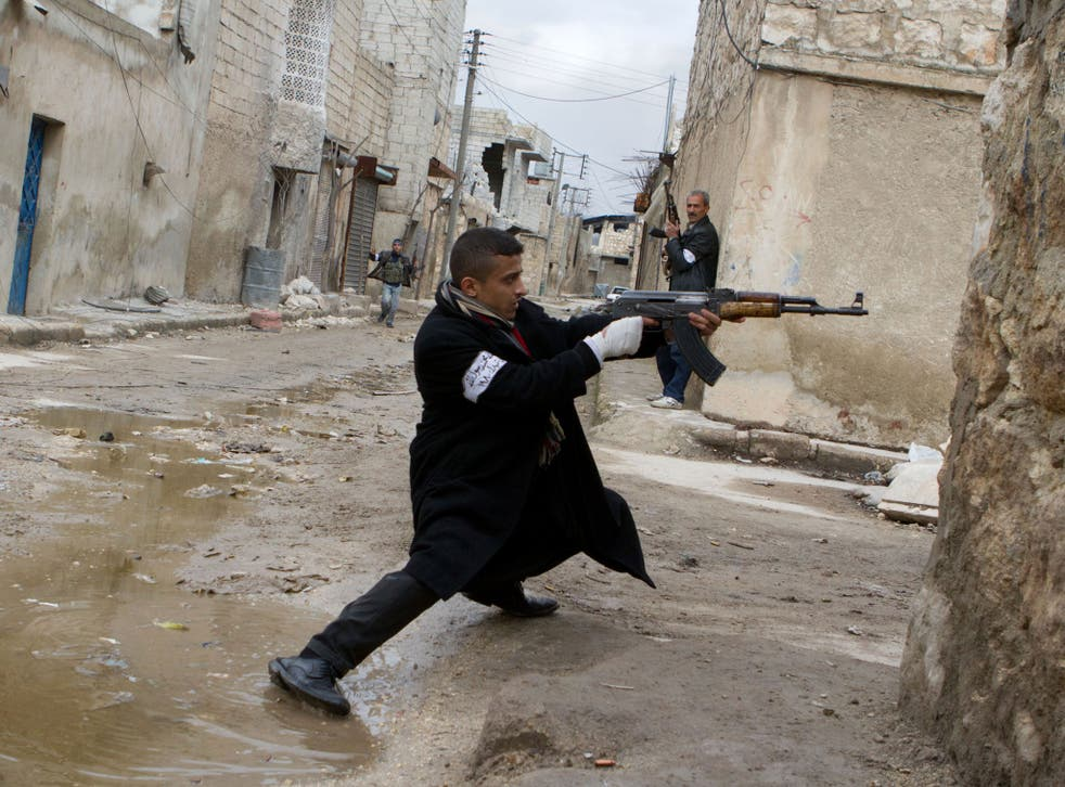 A Syrian rebel aims his weapon during clashes with government forces in the streets near Aleppo international airport in northern Syria on March 4, 2013.