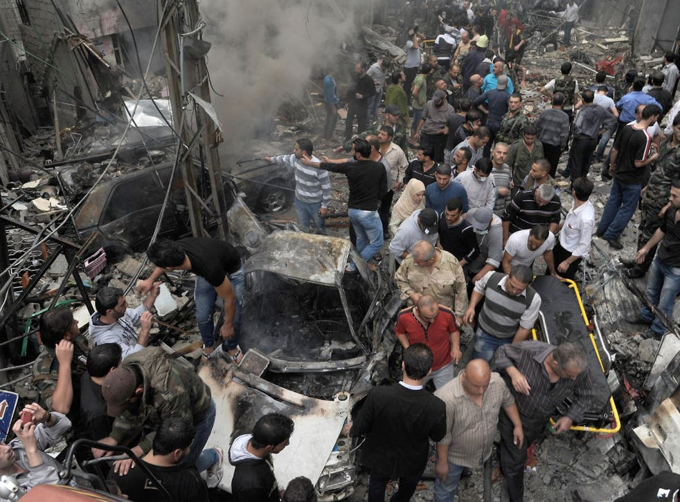 Syrians inspecting the site of an explosion in the Mazzeh district of the capital Damascus.