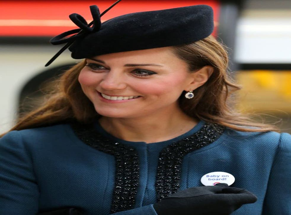 """Kate, Duchess of Cambridge, holds a badge that reads """"Baby on Board"""""""