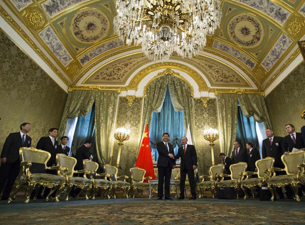 Vladimir Putin and Xi Jinping shake hands in the impressive St George Hall in the Kremlin yesterday