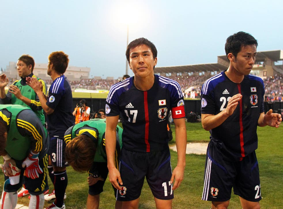 Makoto Hasebe (R) and Maya Yoshida of Japan walk off the field dejected after losing to Jordan