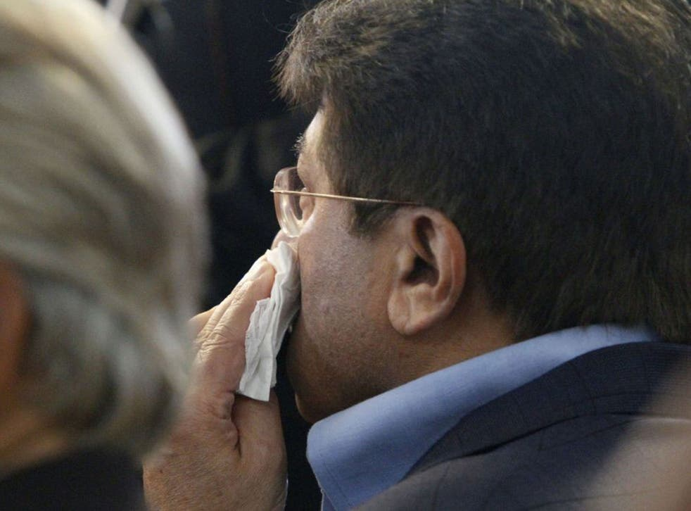 Former Pakistani President Pervez Musharraf wipes his face after a shoe was thrown at him as he headed to court to face legal charges in Karachi,