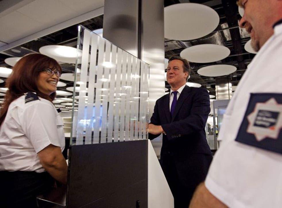 David Cameron with a UK Border Agency official at Heathrow