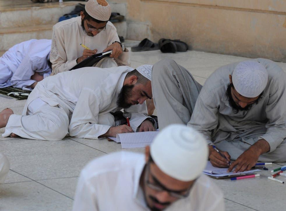 Pakistani youths take exams at an Islamic seminary in Karachi