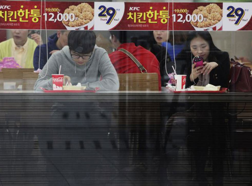 Office workers and shoppers throng the night-time streets of Seoul
