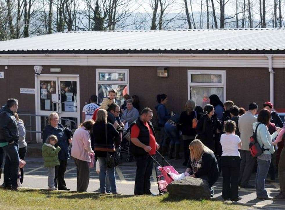 Parents and children queue outside the Paediatric Outpatient department at Morriston Hospital in Swansea