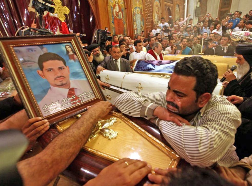An Egyptian Coptic Christian mourns over the coffin of a relative killed in clashes yesterday, during the funeral mass at the Abbassiya Cathedral, in Cairo today