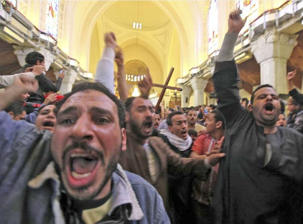 Mourners at St Mark's Coptic cathedral in Cairo carry the coffin of one of the Egyptian Christians killed in sectarian clashes on Saturday