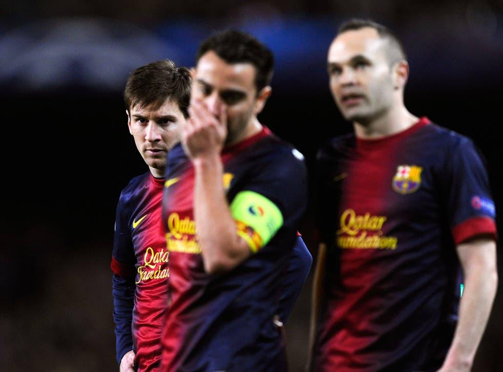 Lionel Messi behind team-mates Xavi and Iniesta