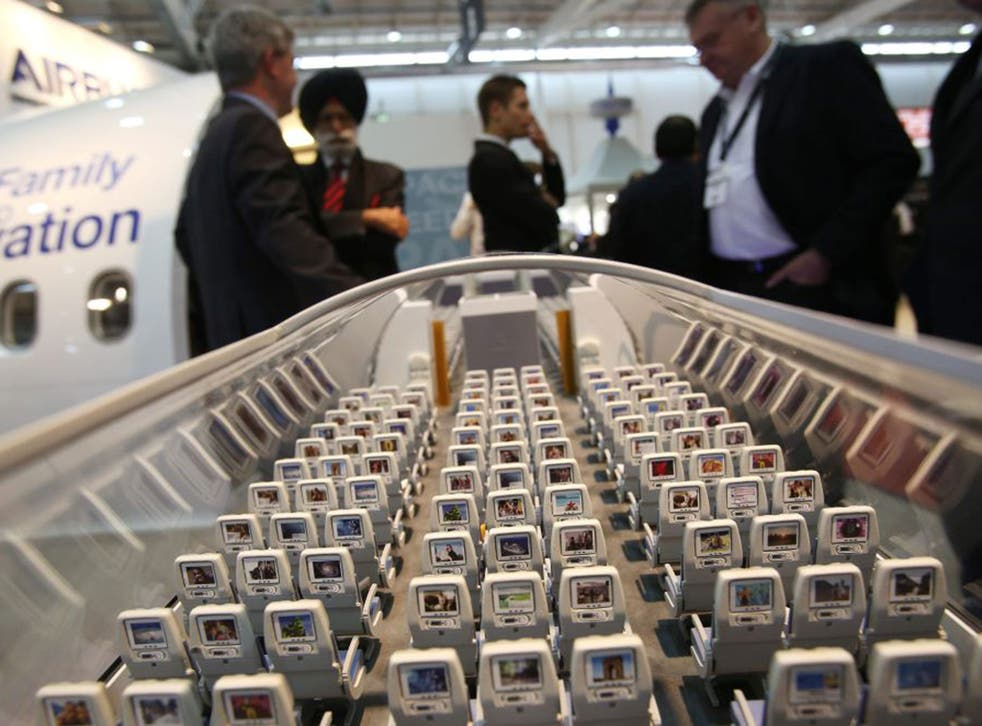 Visitors look at a scale model of an Airbus A350 at the Aircraft Interiors Expo 2013 in Hamburg