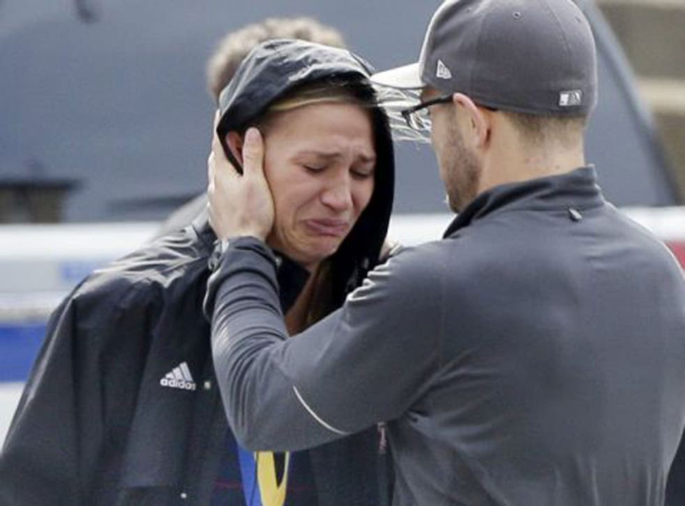 An unidentified Boston Marathon runner is comforted as she cries in the aftermath of two blasts which exploded near the finish line of the Boston Marathon