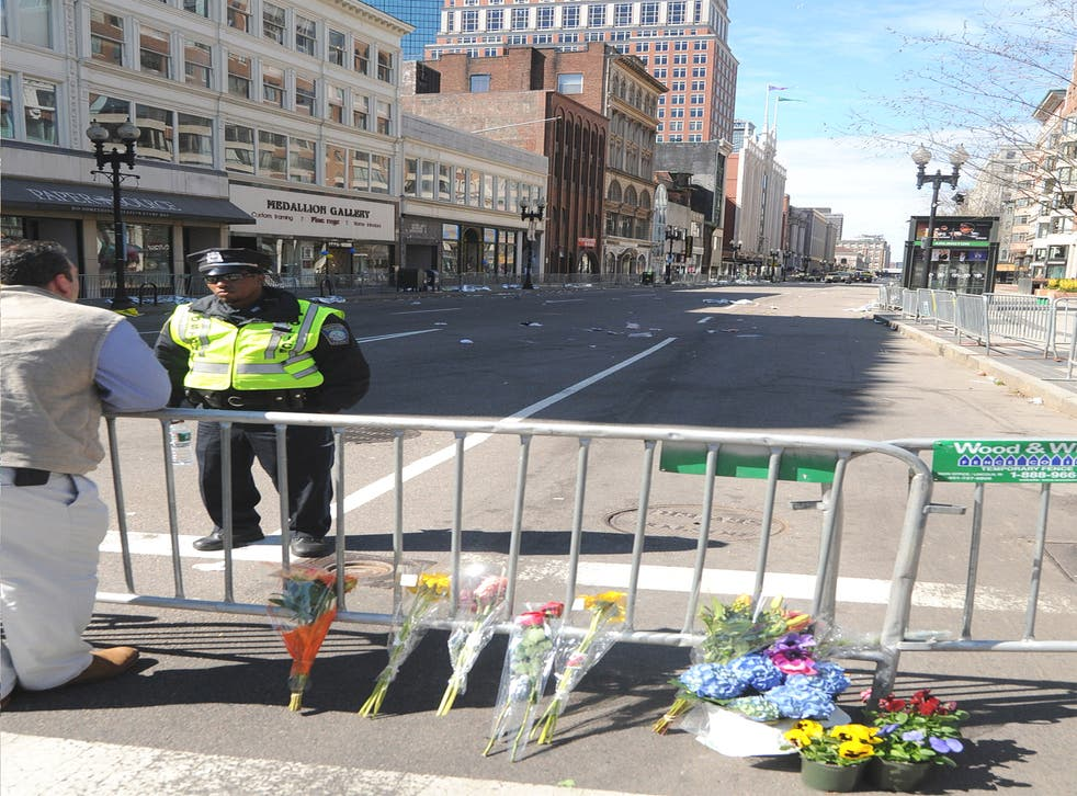 Flowers laid at a barricade on a deserted Boylston Street