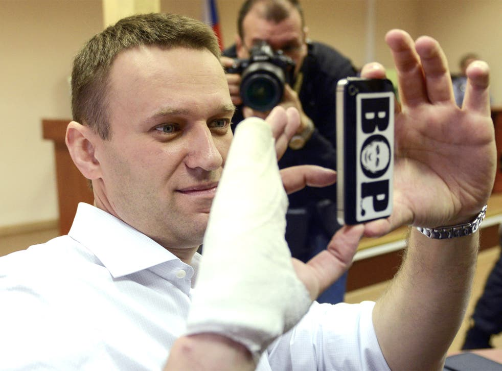 Russian opposition leader Alexei Navalny takes photos on his smartphone during his court appearance in Kirov