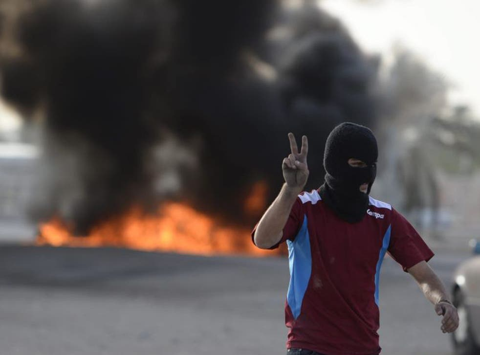 An anti-F1 protester flash the 'V' sign after setting tyres on fire to block a road in Sanabis village, on the outskirts of the Bahraini capital Manama
