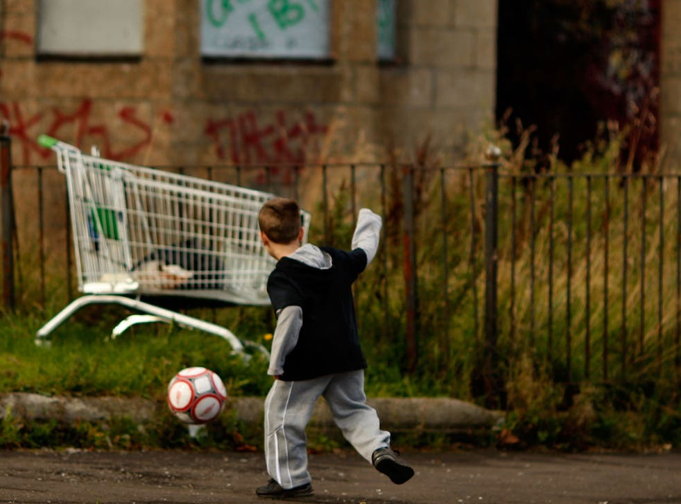 A young boy play's football in a street in Govan